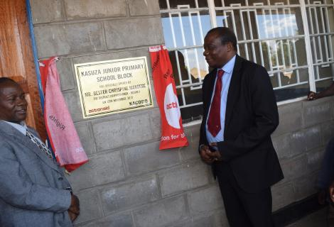 Golowa (Right) and Council Rep, Regson Nkolongo unveiling the plaque to mark the official handover of the school