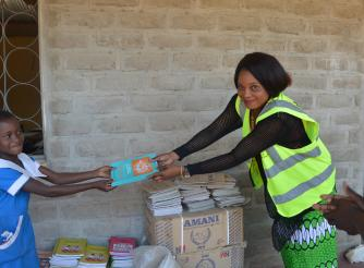 Kuchene Women Forum Director, Getrude Kaleso (Right) making a symbolic donation of books to learners at Thangazi One primary school