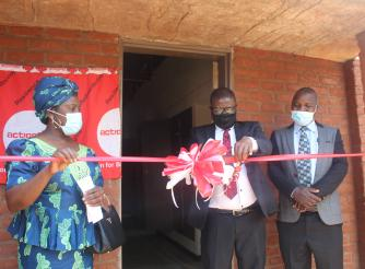 CEED Manager, Billy Banda (flanked by ActionAid Malawi Vice Chairperson, Professor Dorothy Nampota, and Senior Chief Kasakula  cutting the ribbon to mark the official opening of the hostel